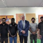 governor smiles at camera with men in front of artwork