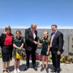 governor shakes school student hand in front of war memorial