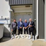 governor poses for photo with men in front of warehouse