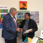 governor receives gift from man and smiles