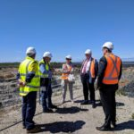 governor poses for photo in front of mining pit with men in high vis vests