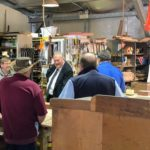 governor speaks to men in shed