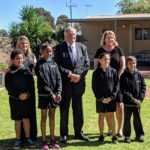 governor stands with children for photo in school garden