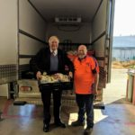 governor holds box of food with man in front of truck