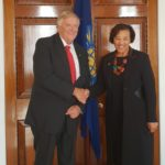 governor and woman pose for photo in front of door