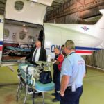 governor looks at staff operating aircraft in hanger