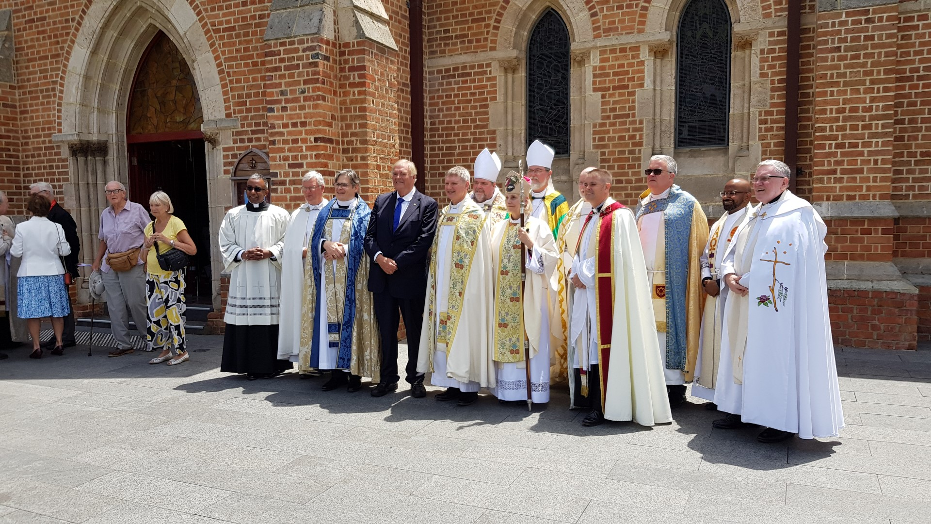 Govenror stands with anglican clergy outside church