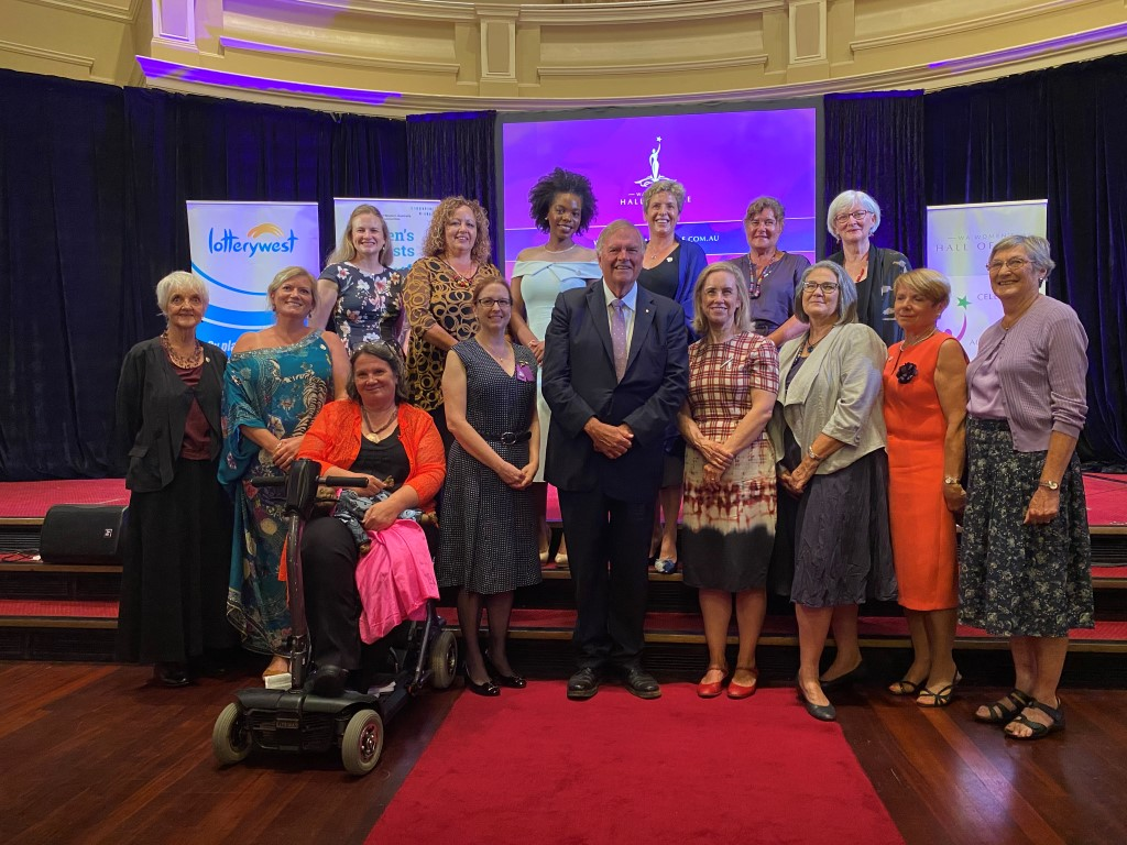 governor poses for group photo with women in ballroom