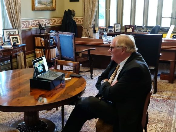 The Governor sitting on zoom meeting with two guests