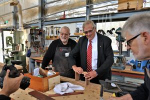 governor sands a piece of wood in a workshop