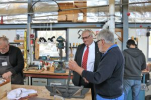 governor speaks with technician in a workshop