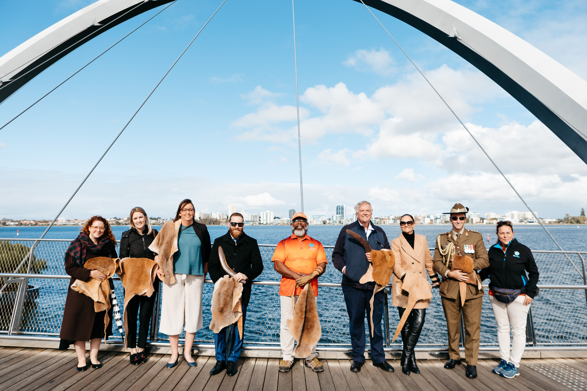 The Governor and Ms Annus with five staff members and tour guides standing on bridge