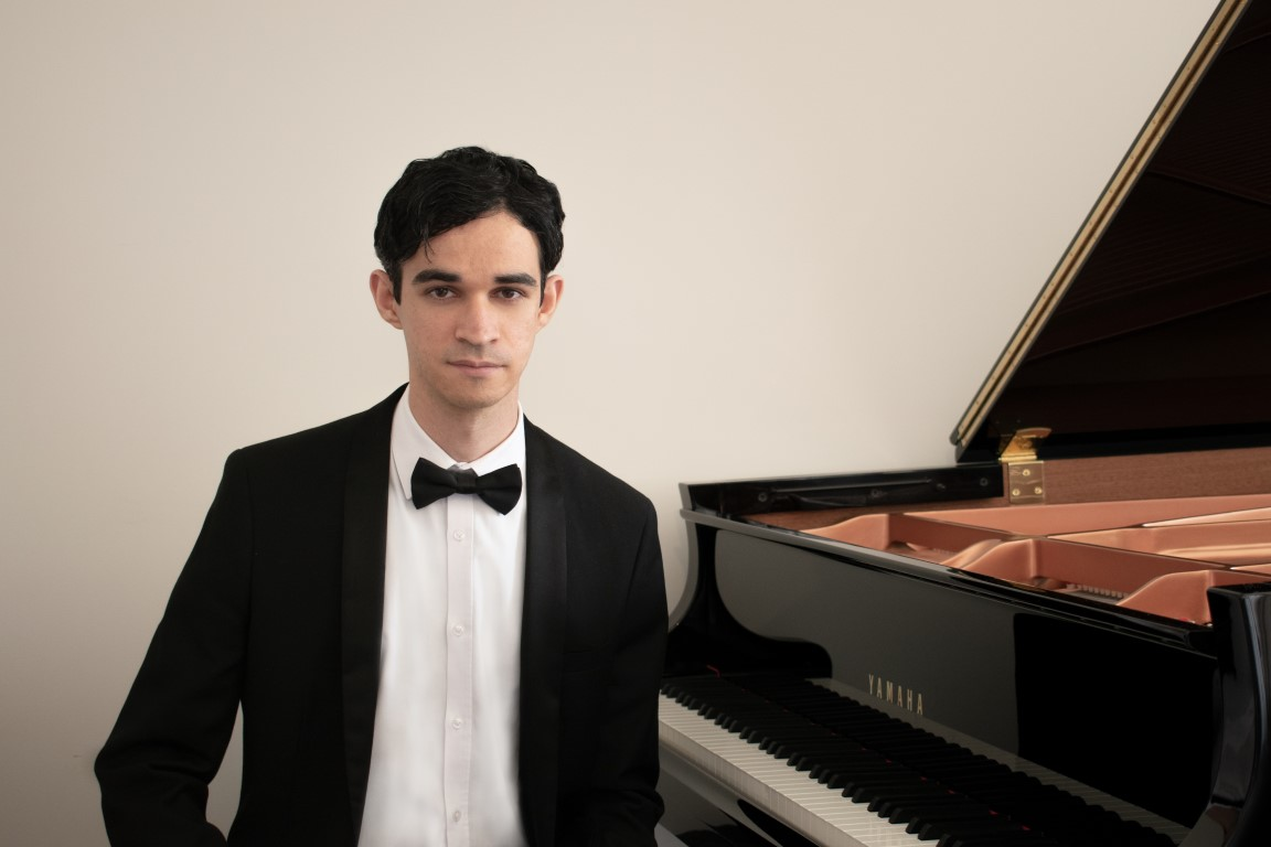 man stares at camera sitting next to piano in formal wear